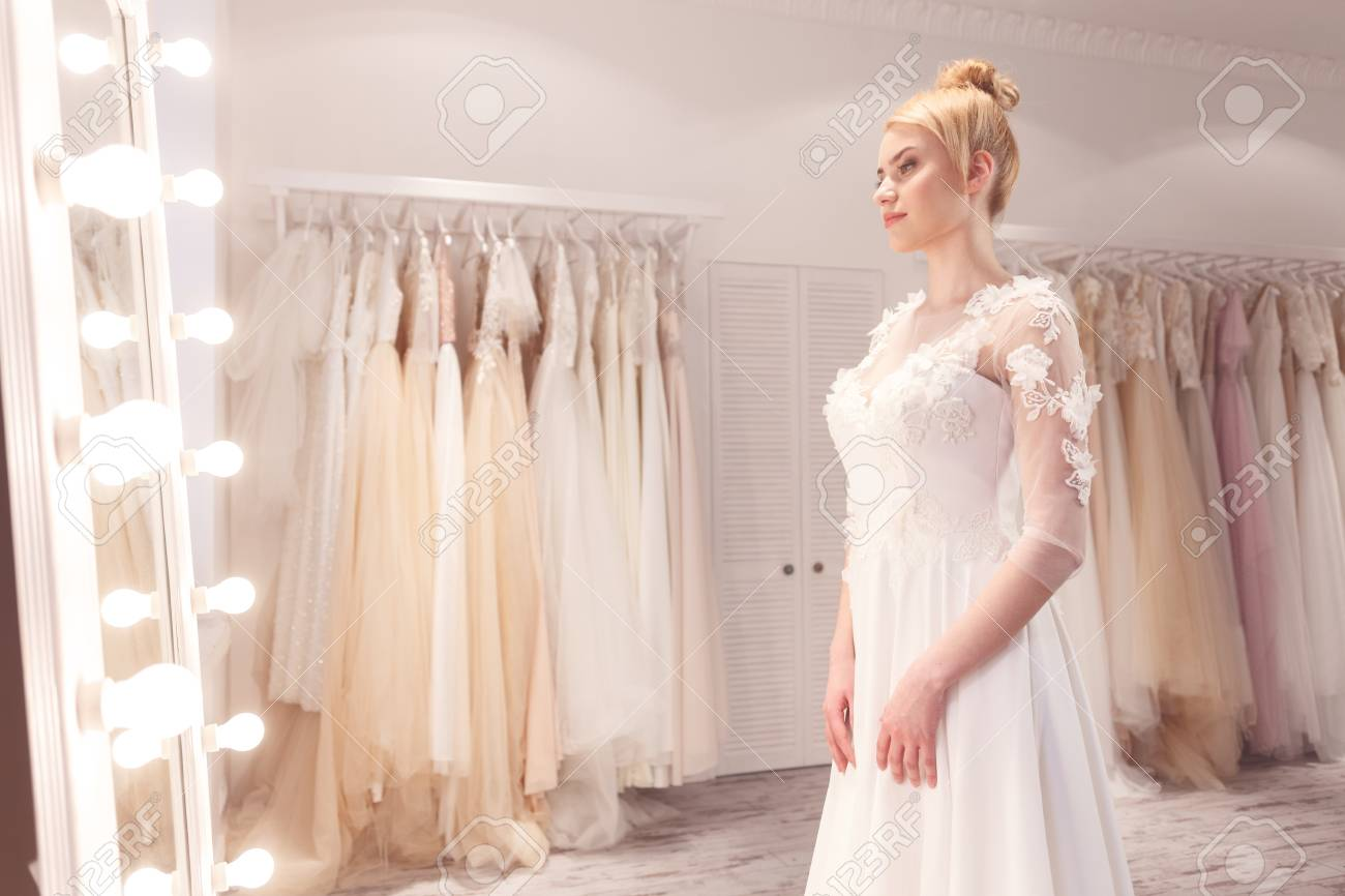 Attractive Bride Is Wearing A White Wedding Dress She Is Standing