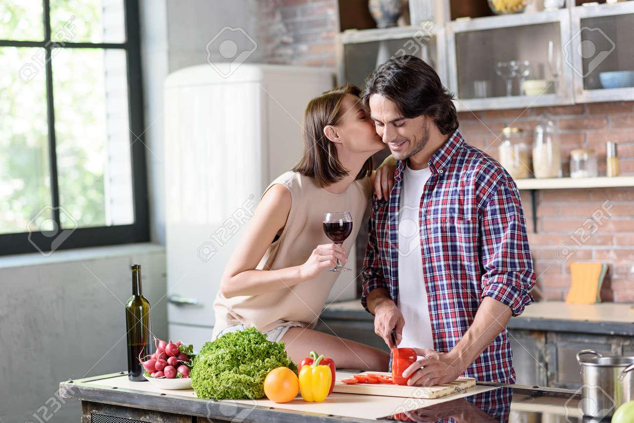 Jeune Homme Prépare Le Dîner Romantique Pour Sa Femme Il Est La Coupe De Légumes Et Souriant La Femme Est L Embrassait Avec Amour Elle Est Assise