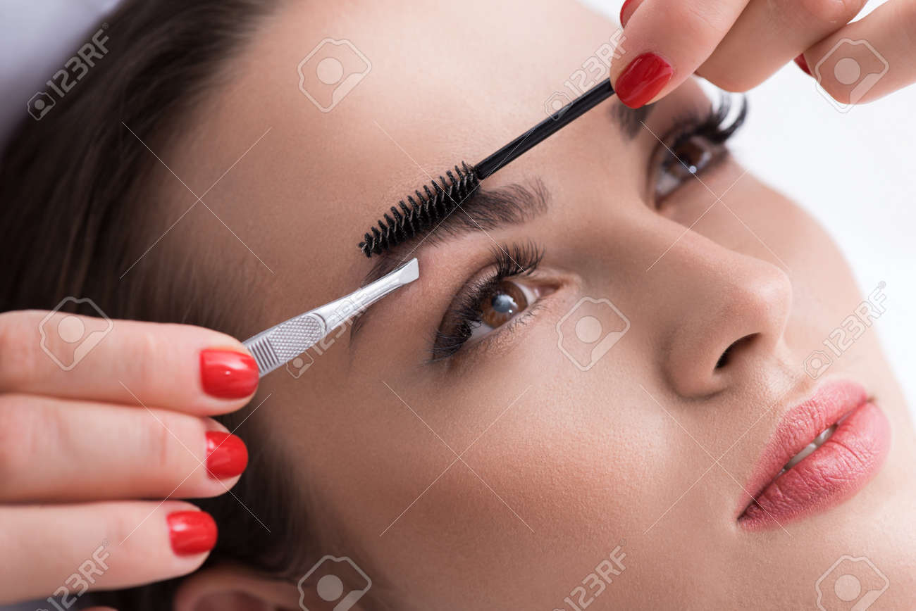 Close Up Of Cosmetician Hands Pulling Out Female Eyebrows By Stock