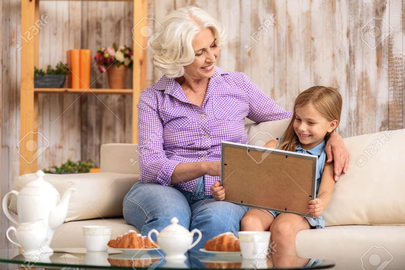 Feliz Abuela Y Nieta Están Viendo La Foto En Marco Con Interés ...