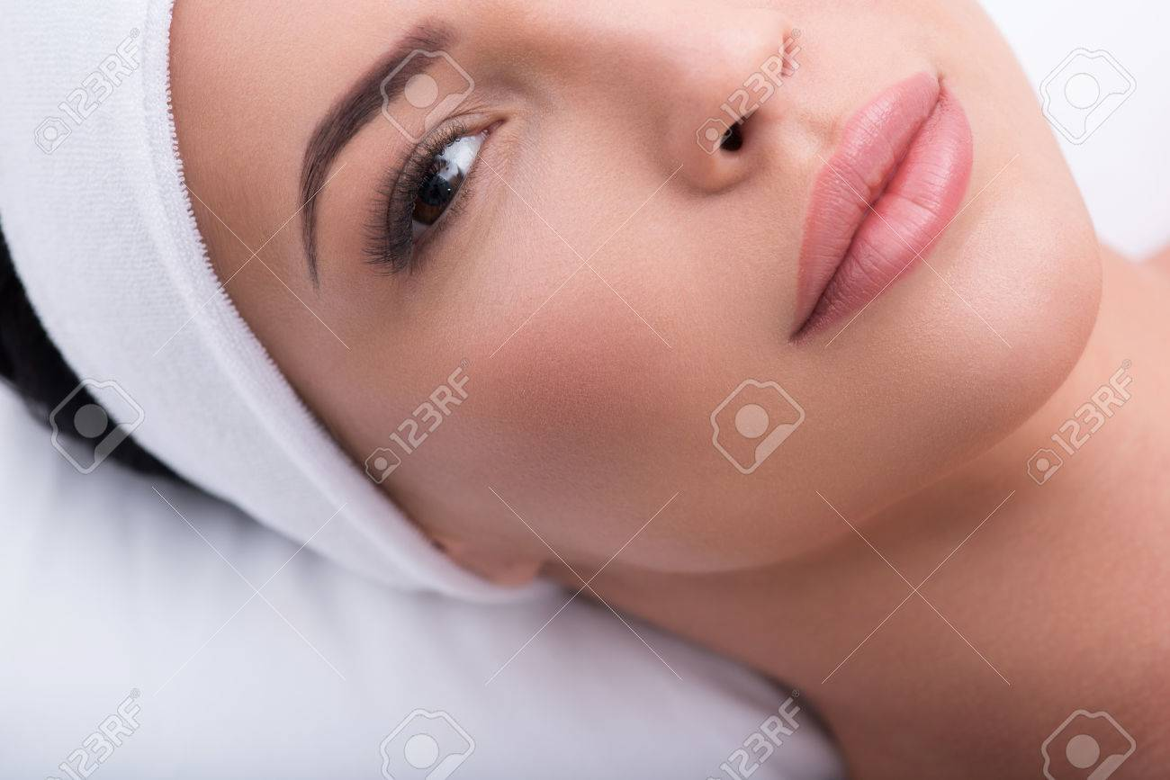 Top view close-up of beautiful woman with lengthened eyelashes. She is lying and looking at camera with confidence - 64880920