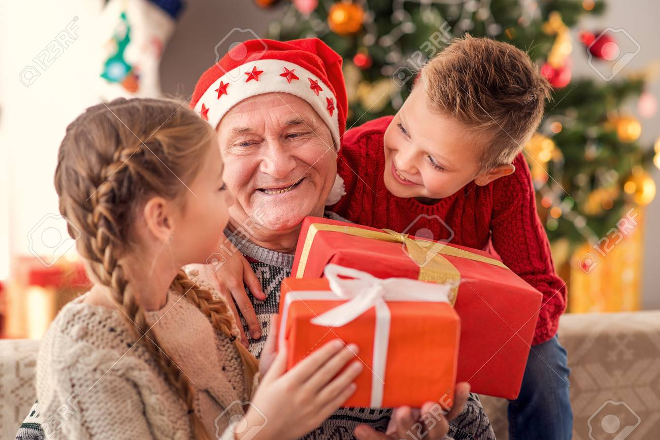 Happy Children Are Receiving Christmas Gifts From Grandfather ...