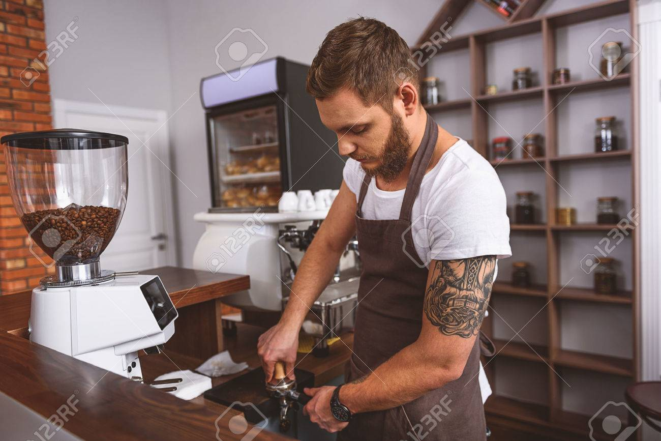 bearded handsome barista using a tamper to press coffee beans Foto de archivo - 66014736