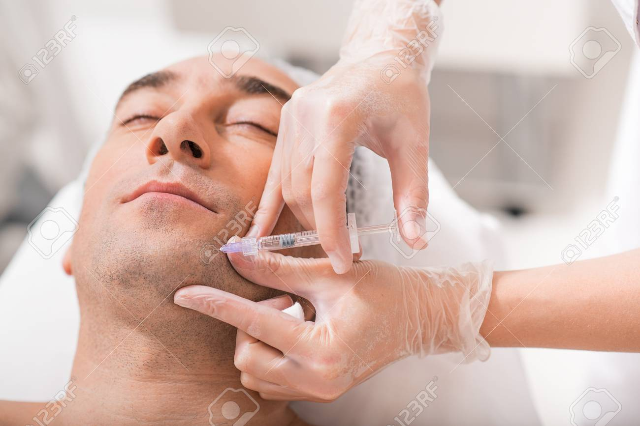 Close up of skillful beautician hands preventing facial skin