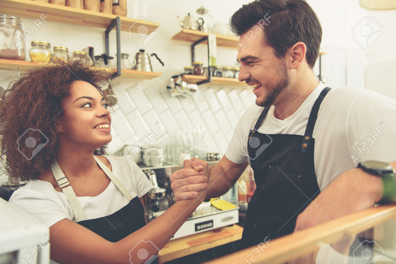 Happy female and male baristas joying at work station