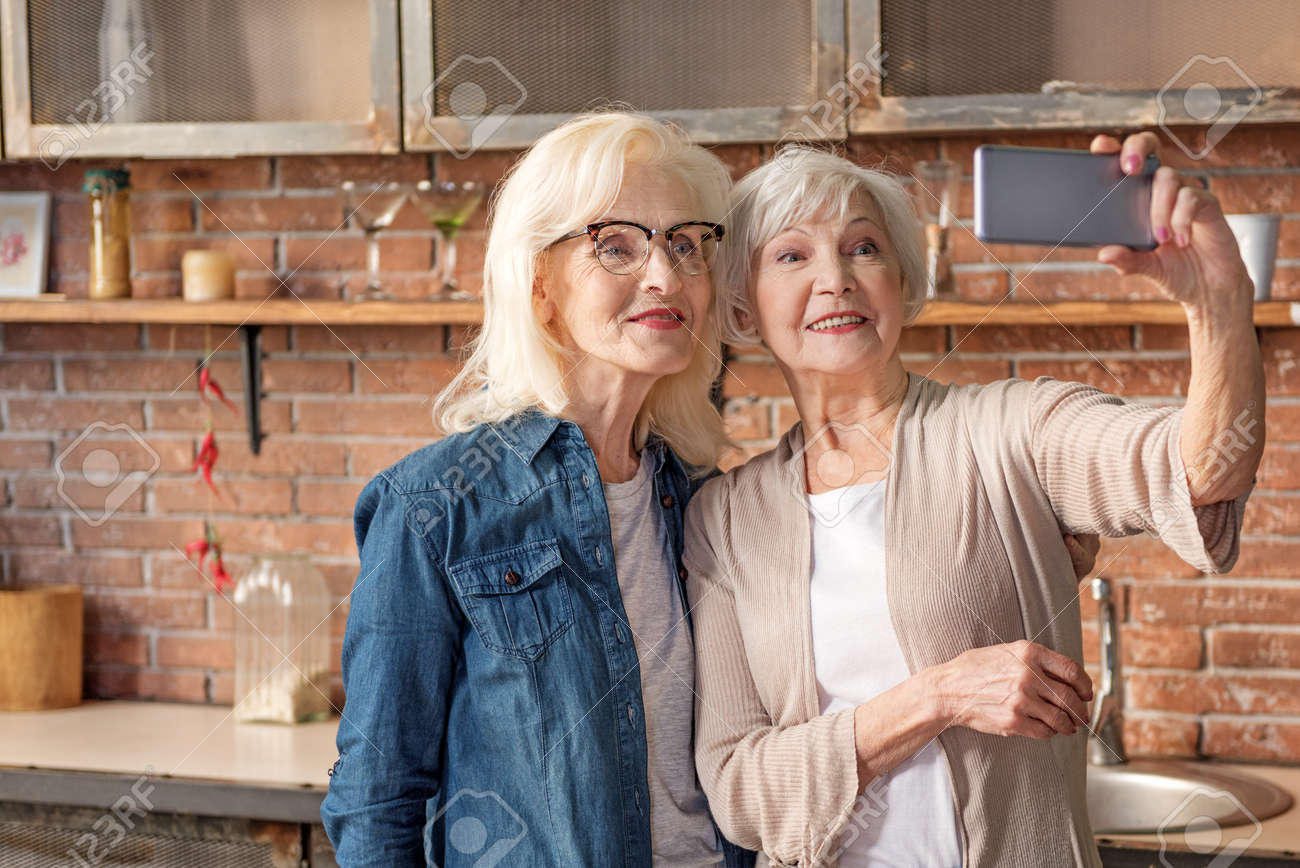 Abuelas Maduras abuelas modernas divirtiéndose con smartphone