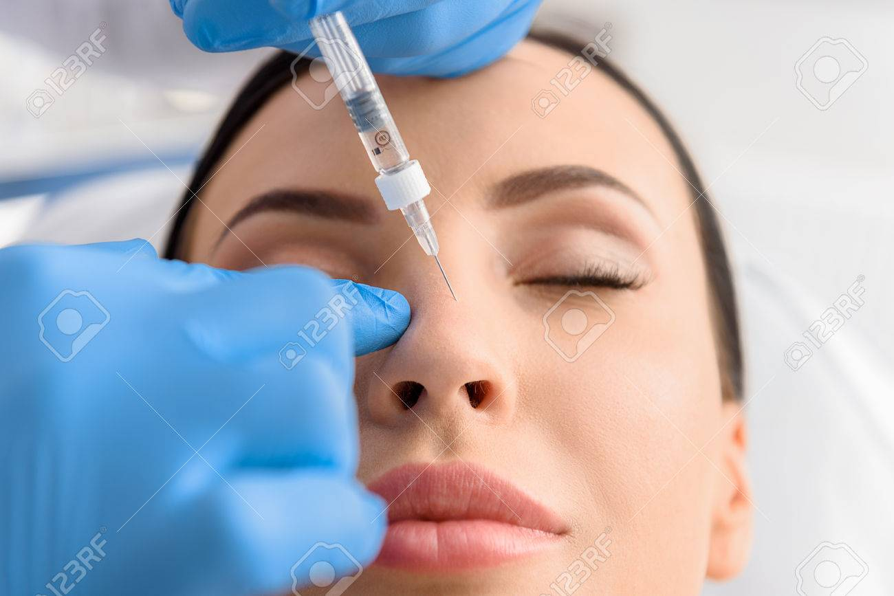 Serene female receiving collagen in nose - 78448660