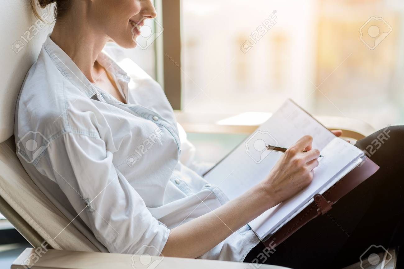 joyful elegant woman writing down comment in journal stock photo