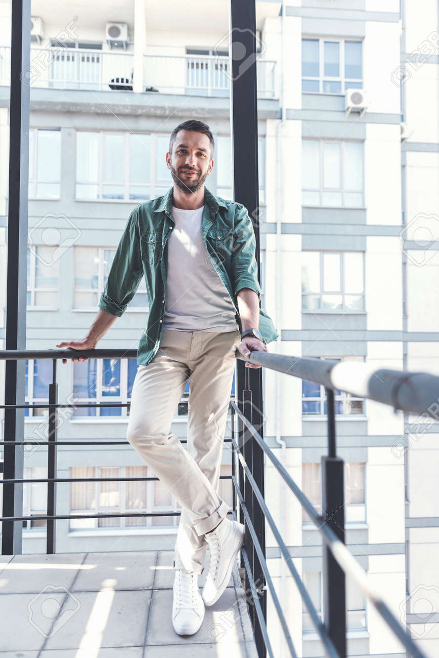 positive man is leaning on railing stock photo picture and royalty