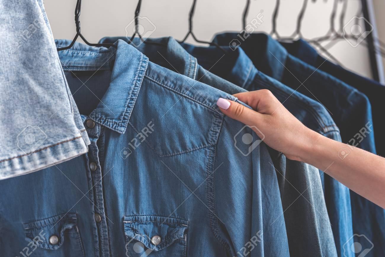 La Chica Va A Llevar Una Camisa De Jean Varias Chaquetas Están En Perchas Ciérrese Para Arriba De La Cosa Femenina De La Toma De La Mano Copie El Espacio A La