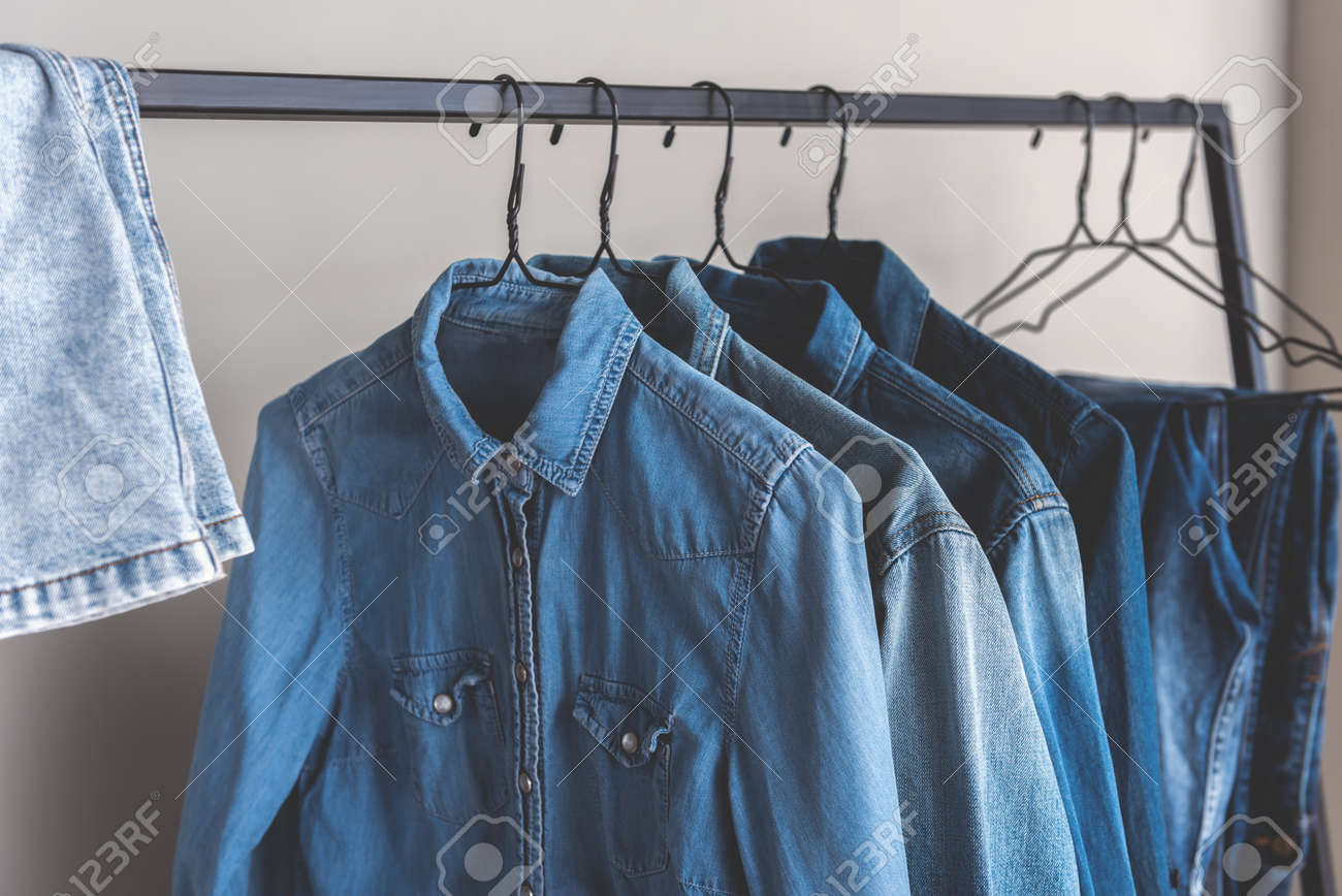 Different Blue Jean Shirts Are Hanging On Metal Modern Hangers ...