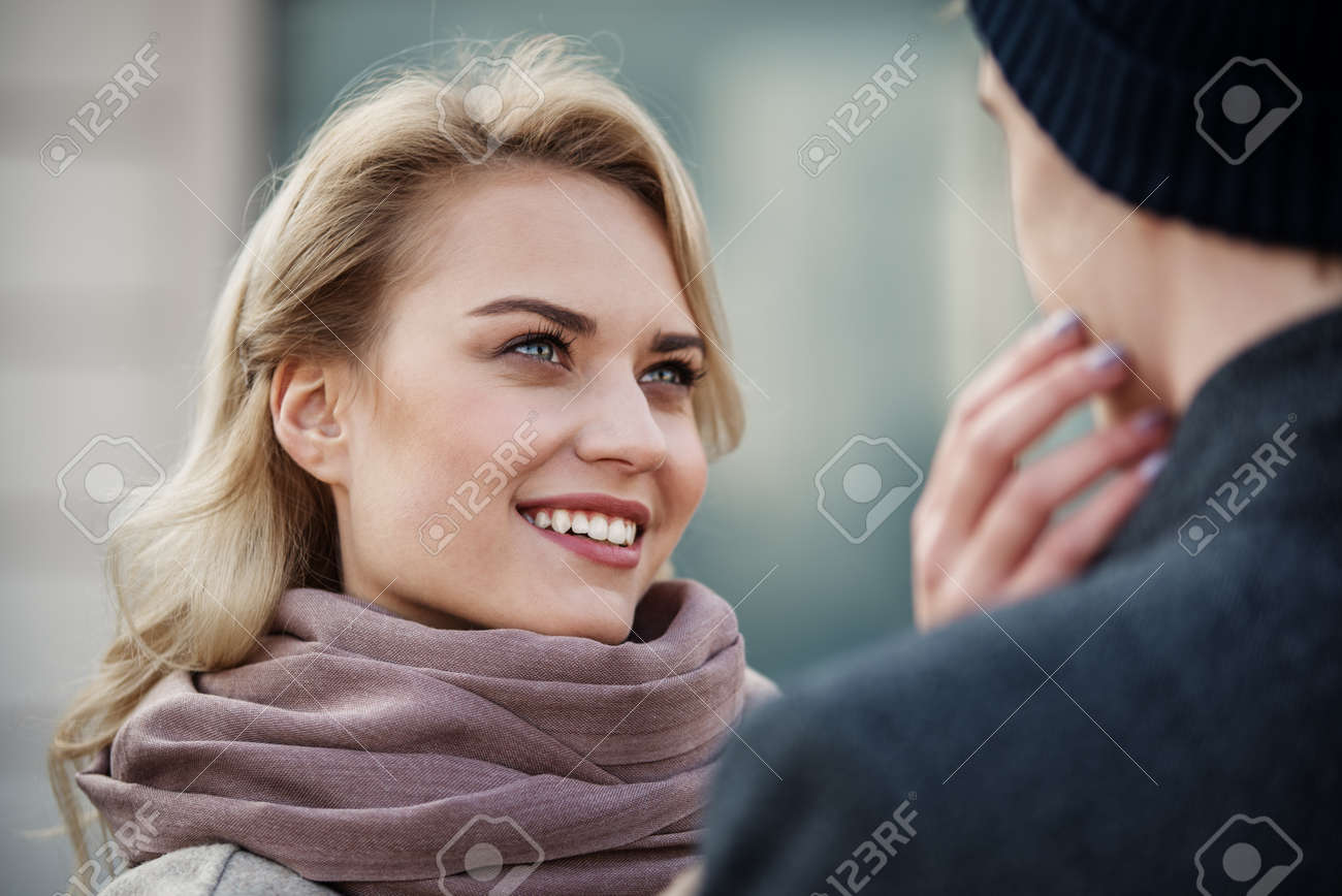 Close up portrait of loving couple standing together. Focus on woman putting hand on head of man - 92055521