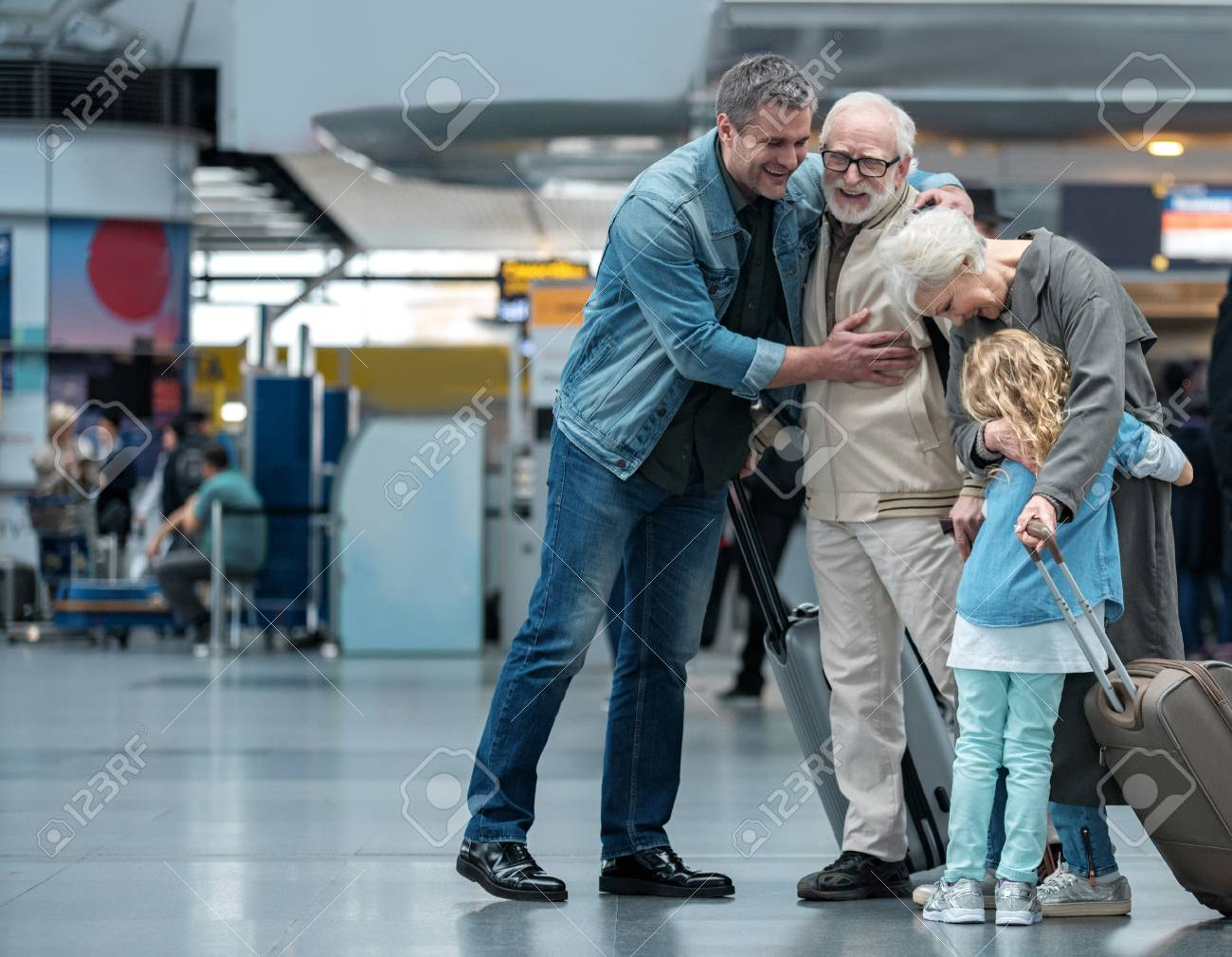 Happies moment. Full length of aged father is hugging his adult sun and expressing gladness. Old joyful woman is embracing her little grandchild while standing in waiting hall at airport. Copy space - 92228583