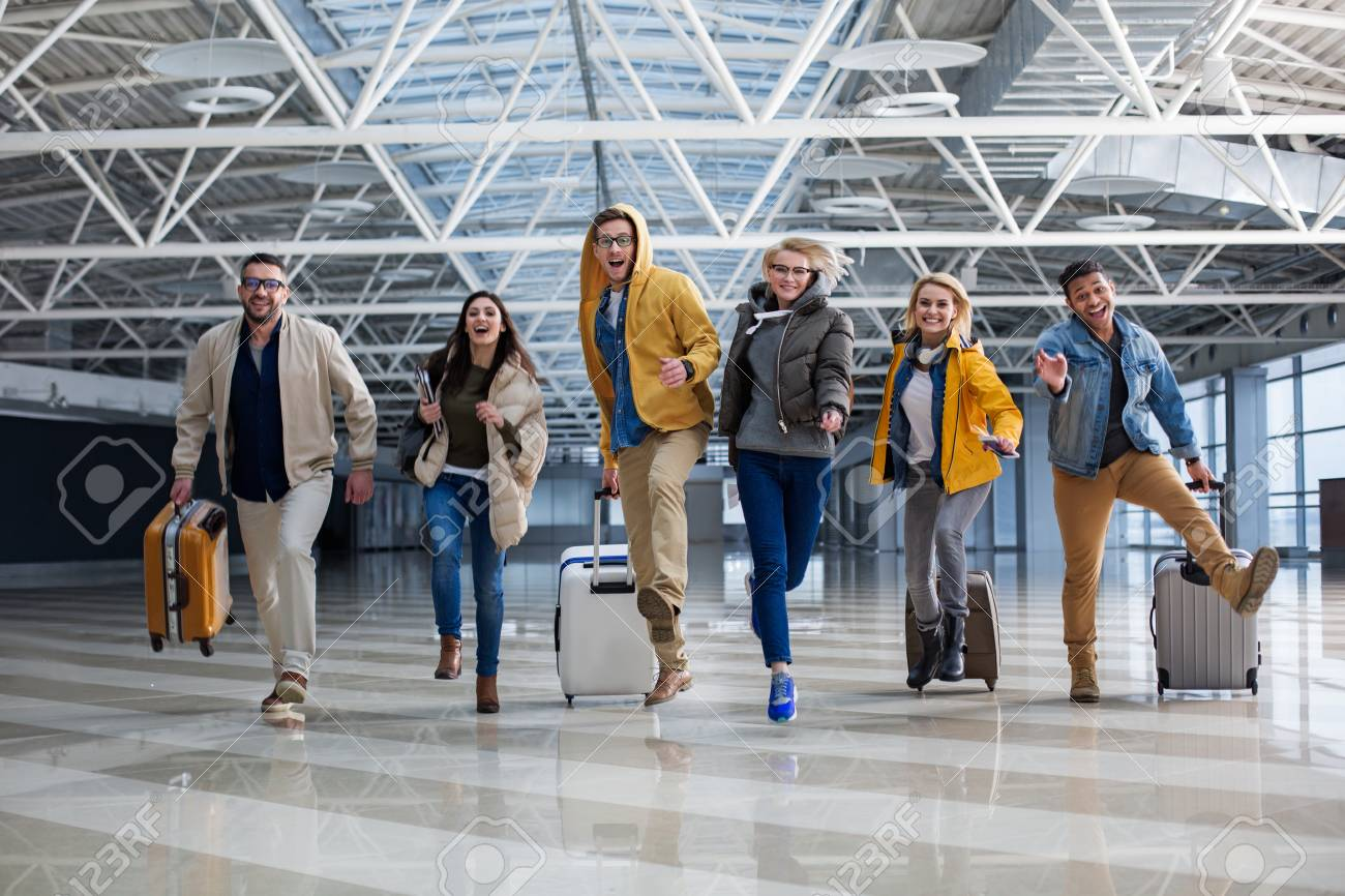 Full length portrait of group of tourist chasing each other at the airport. Their faces are joyous - 95822078