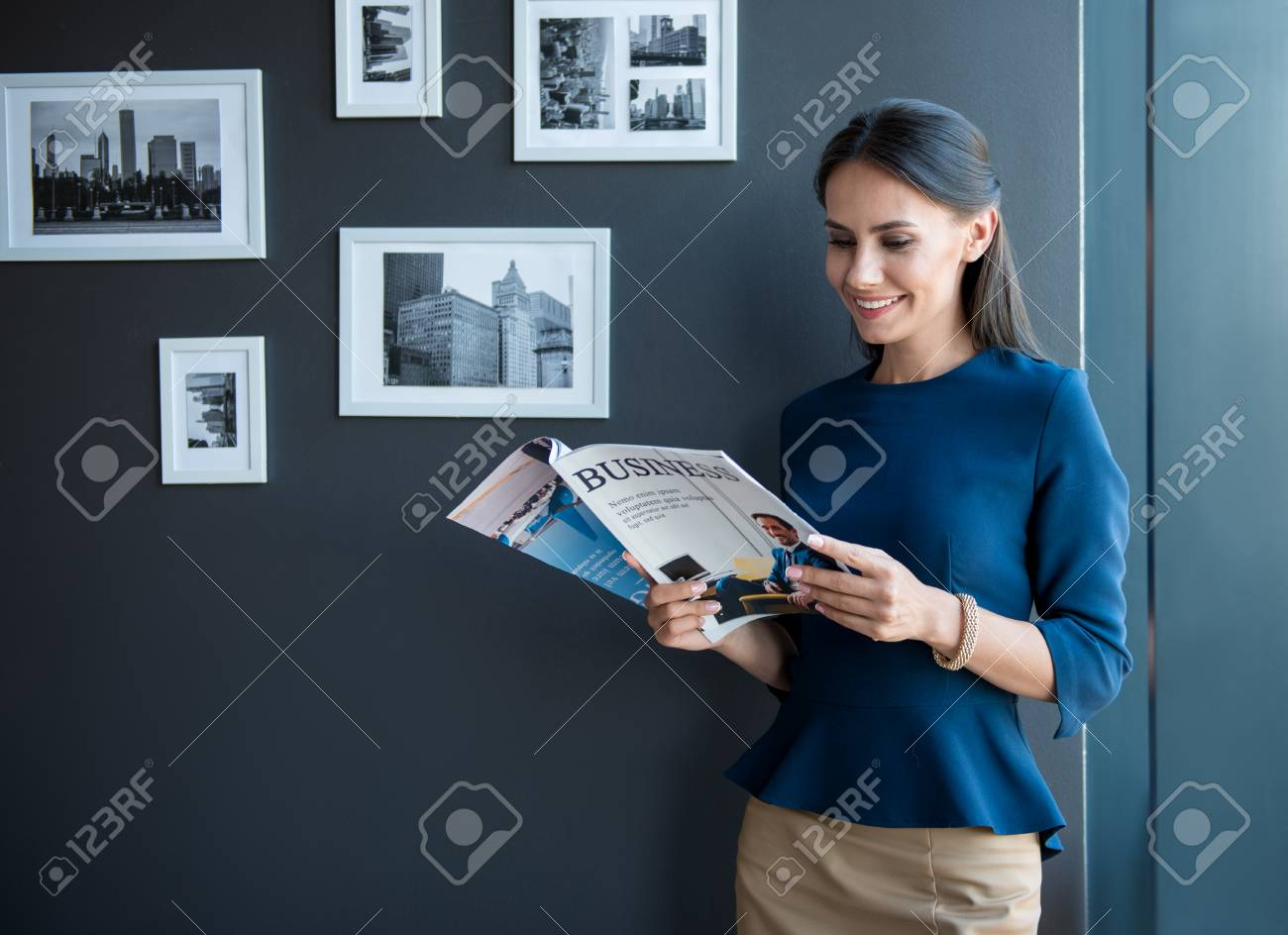 Joyful working time. Optimistic stylish young woman is standing with business magazine and reading with pleasure. She is expressing joyfulness. Copy space in the left side - 96795490
