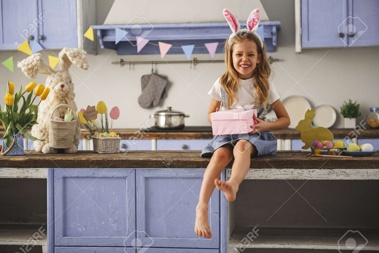 Portrait of glad little girl wearing rabbit ears on head resting in the cozy kitchen with present in hands. Copy space in left side - 96373060