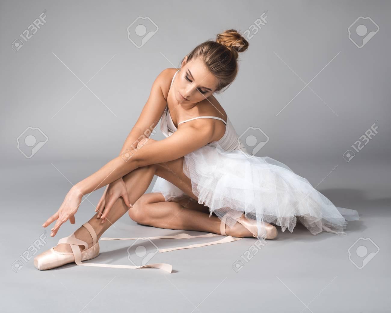 Graceful Ballerina Sitting And Untying