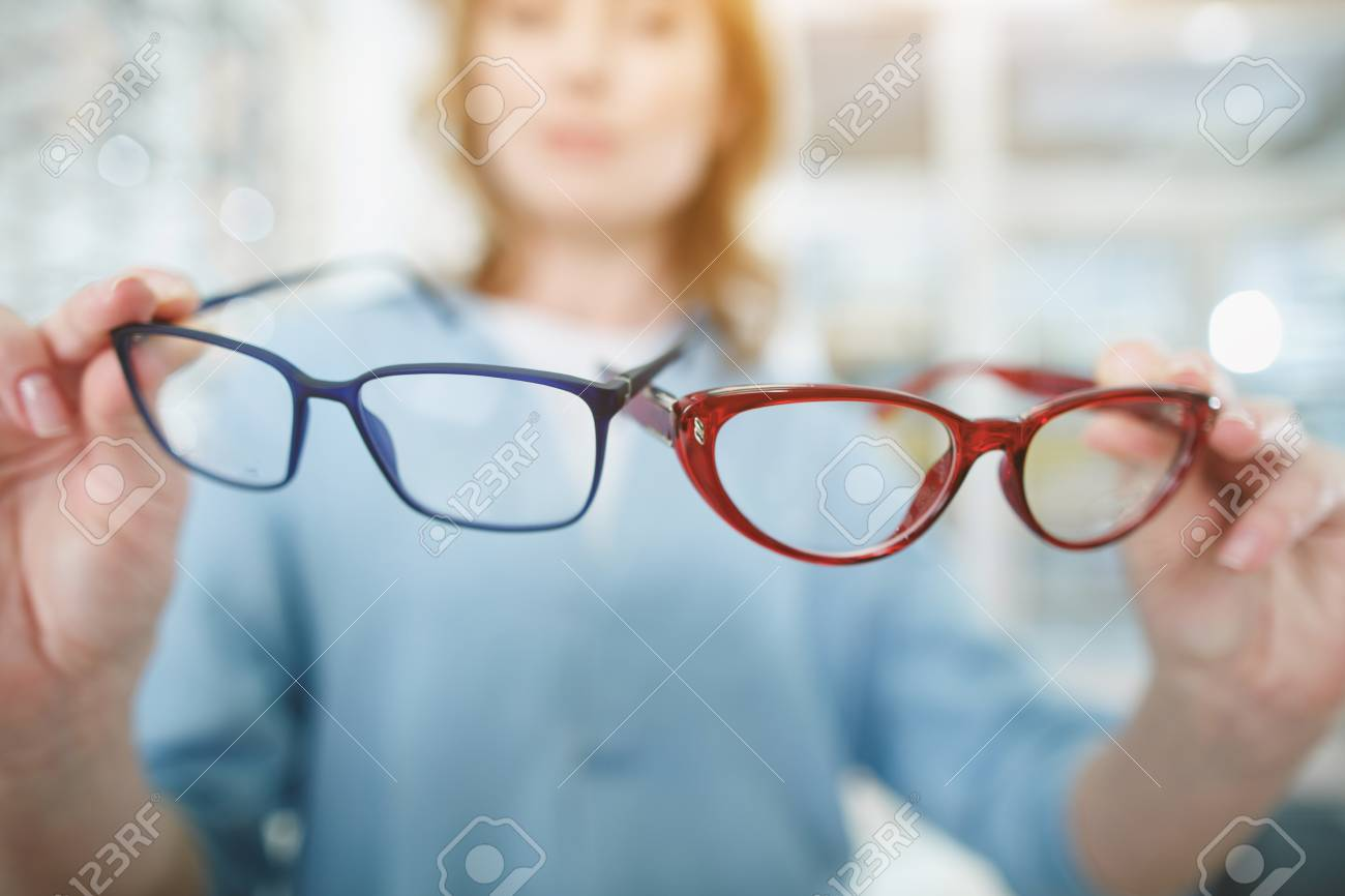 0fb9eb1e214 Close up female hands holding eyeglasses in glasses shop. Ophthalmology  concept Stock Photo - 97246157