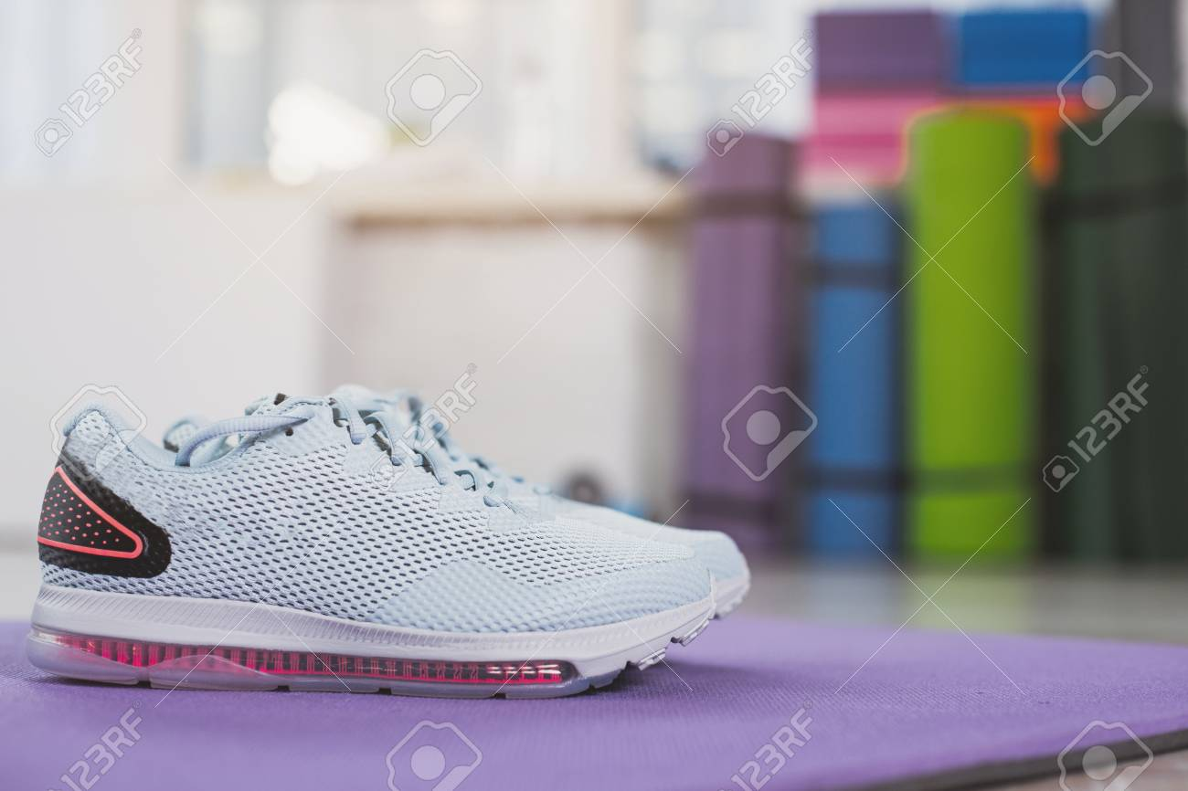3b9214890cad Sport is waiting. Focus close up of blue sneakers put on carrymat with  exercising equipment