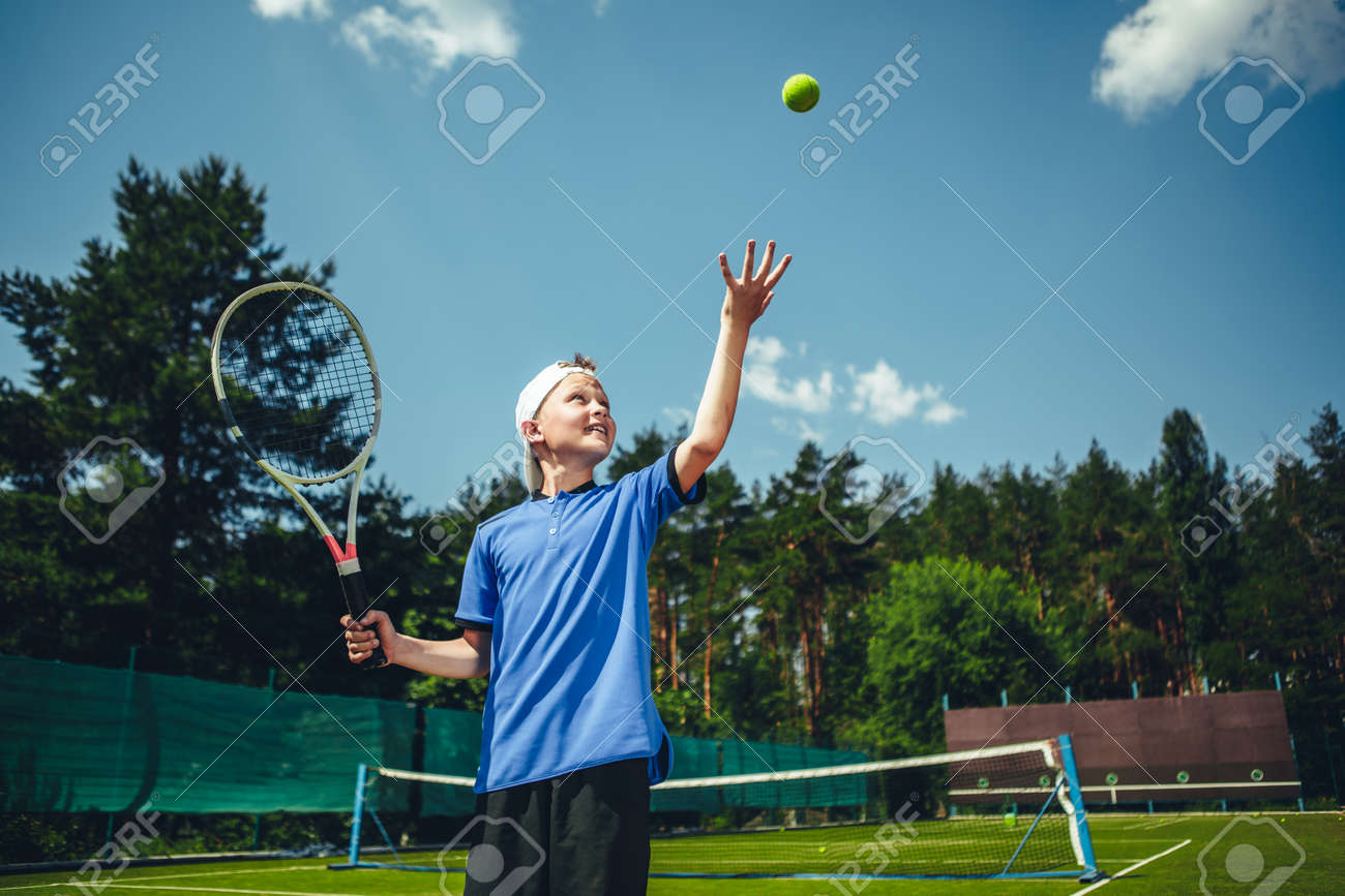 Side View Smiling Child Catching Ball While Holding Sport Tool