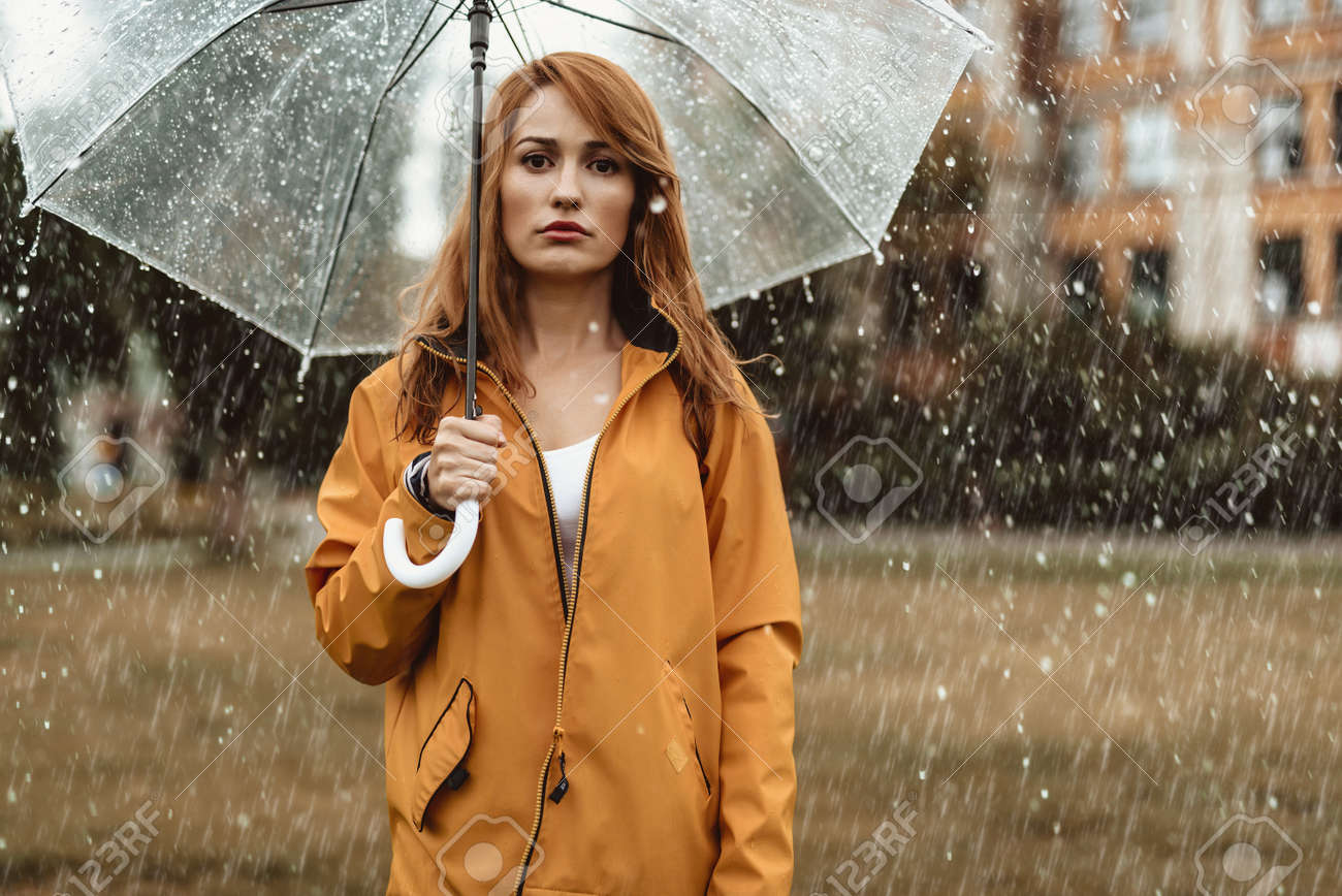 ed00c179c34 Stock Photo - Waist up portrait of unhappy girl holding umbrella in hands.  She is looking at camera with discontent
