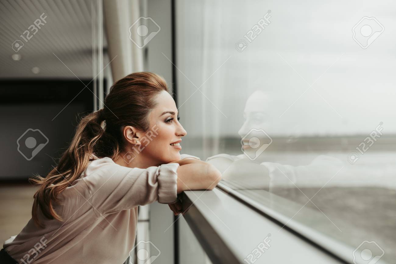 Side view happy woman dreaming while looking at window indoor. She having rest during labor - 105740062