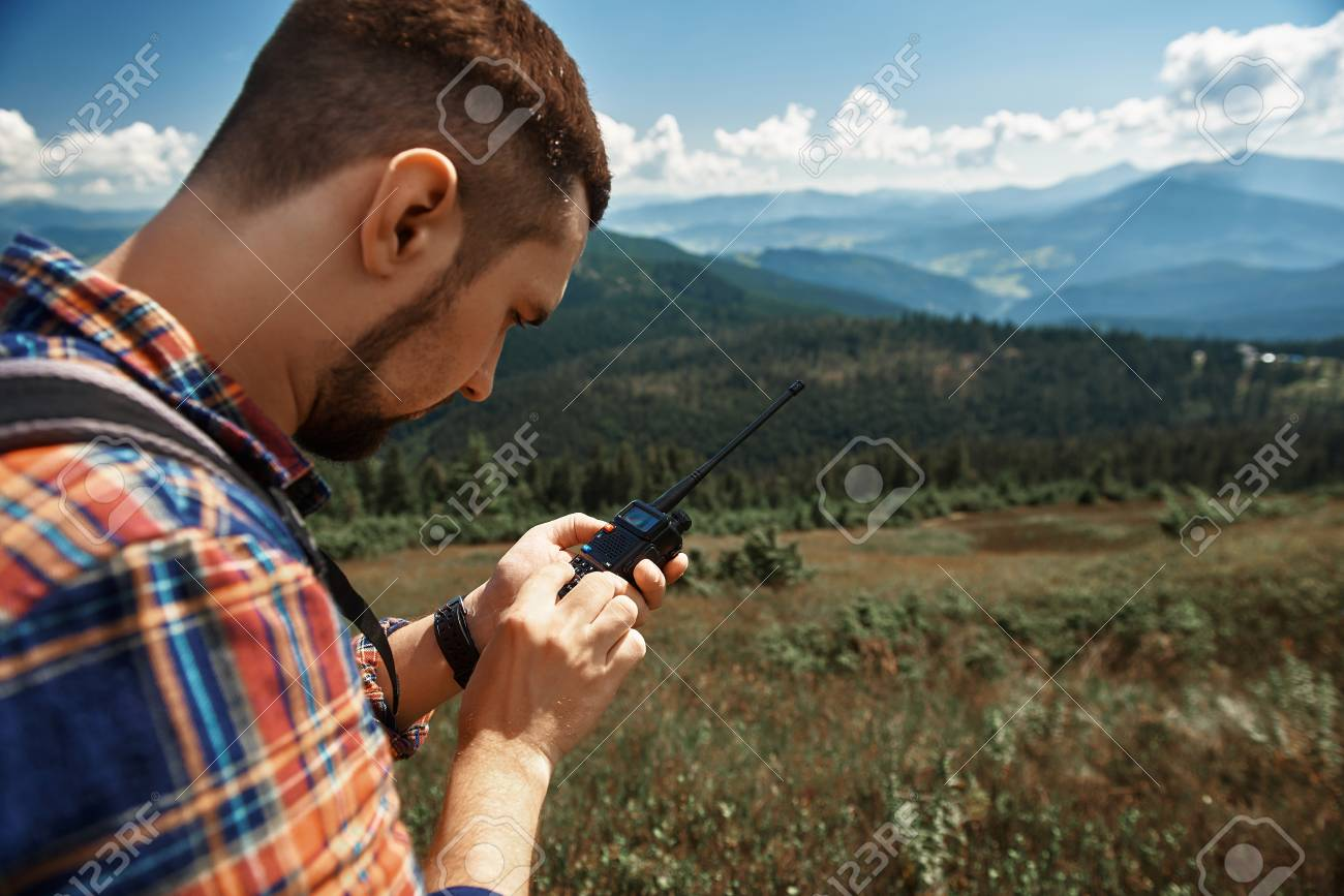 Focus on guy holding walkie-talkie and trying to find connection