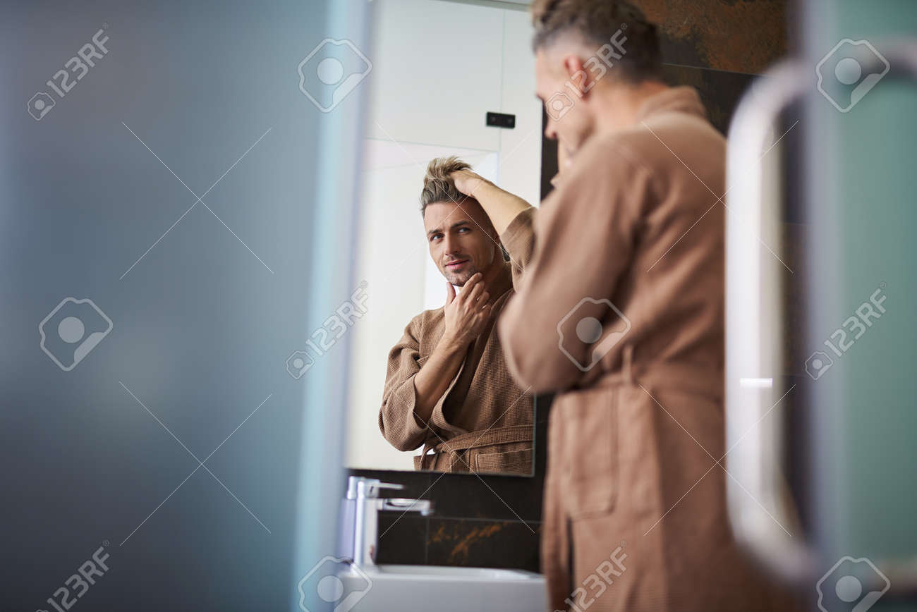 Handsome unshaven gentleman in bathrobe fixing his hair while touching chin and smiling slightly - 114994259