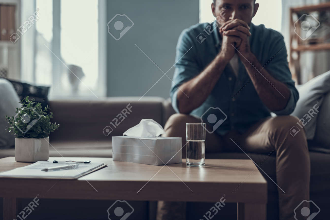 Man sitting on the sofa with his fingers crossed in front of his face and having a glass of water - 114993879