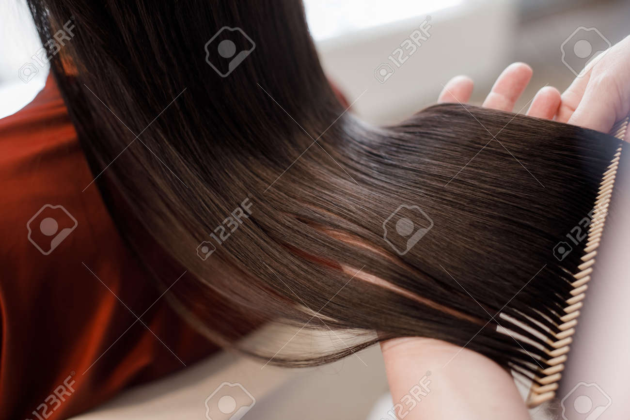 Close up. of beautiful silky hair is in hands of stylist while she combing by hairbrush - 117442043