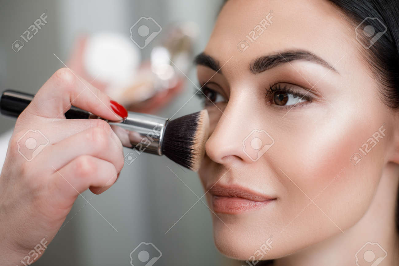 Close up of makeup artist applying light layer of matting powder while using professional brush for lady - 116484083