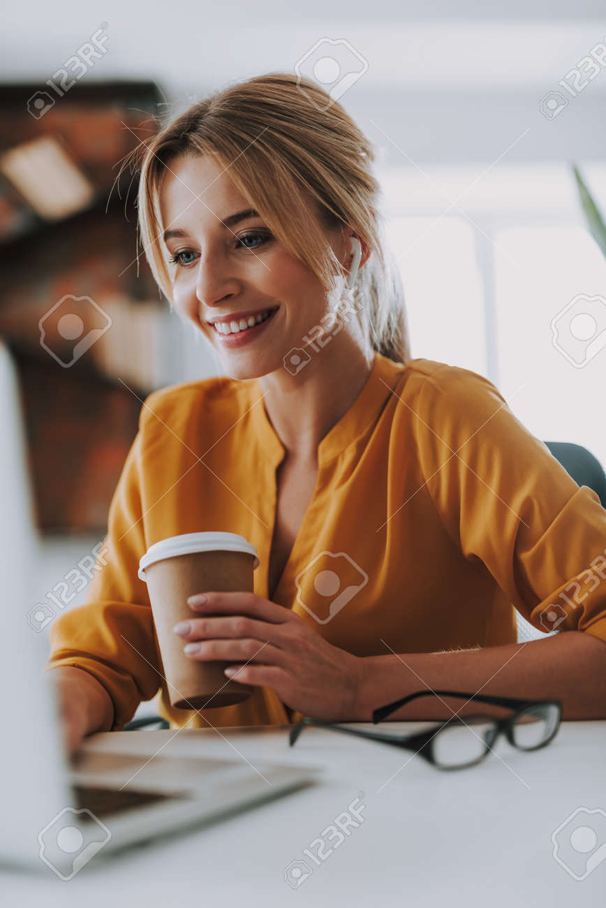 Woman with earphones working on the laptop - 122925612