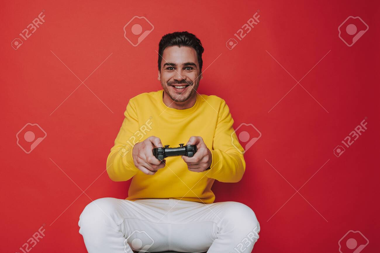 Half length of cheerful brown-haired guy holding joystick on red background - 124533836