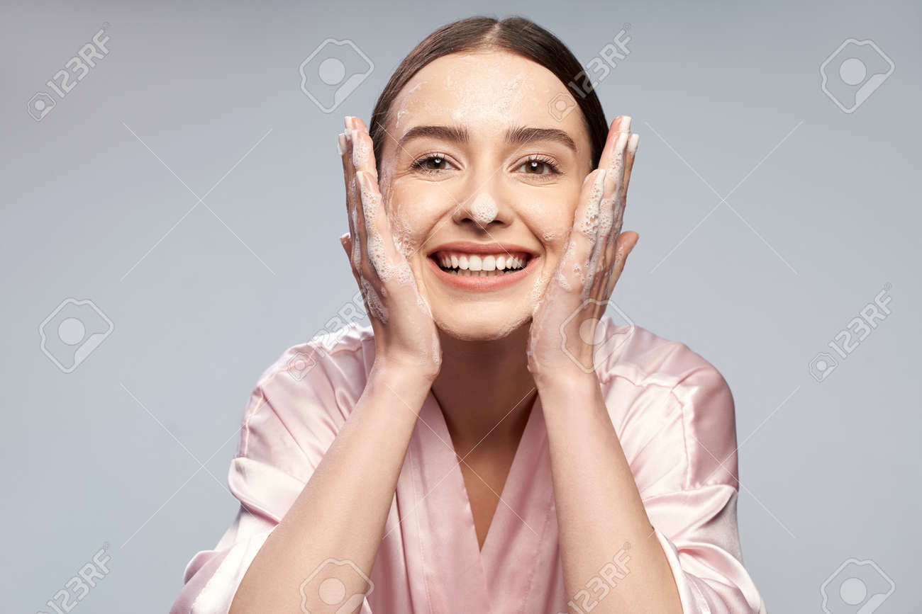 Cheerful pretty girl washing face with foaming cleanser - 126646674