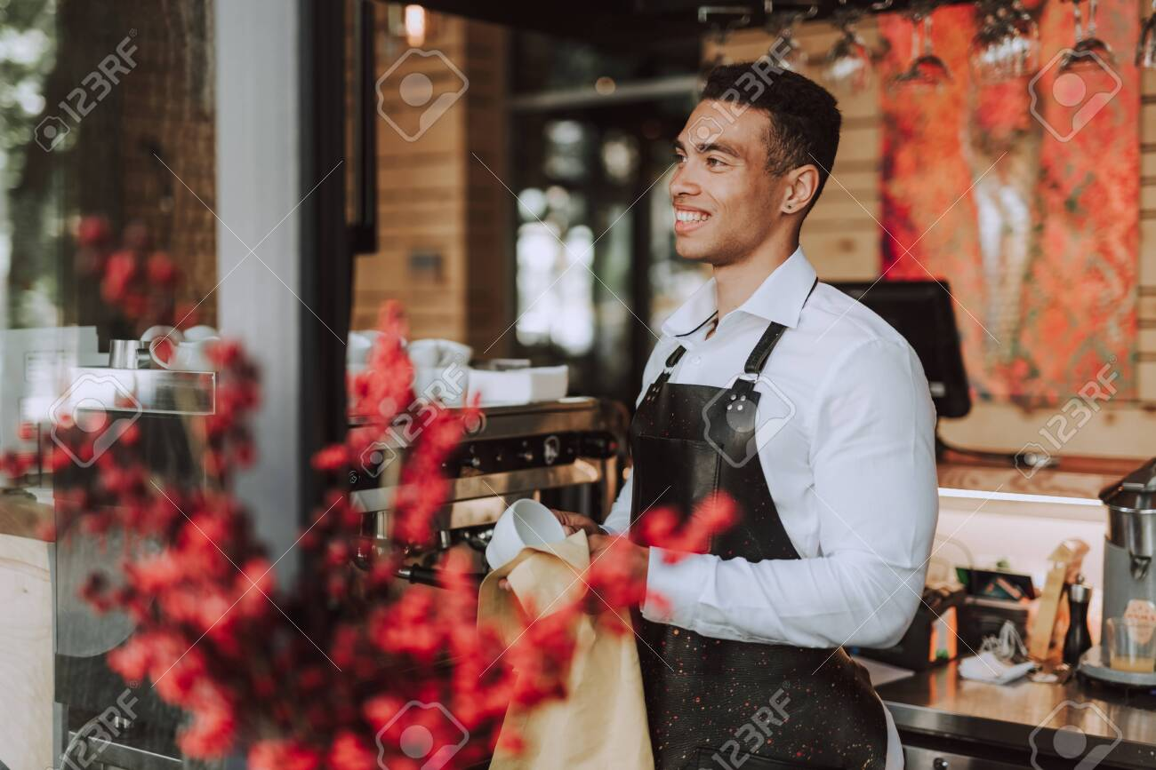 Handsome barman wiping white cup with cleaning cloth - 128362263