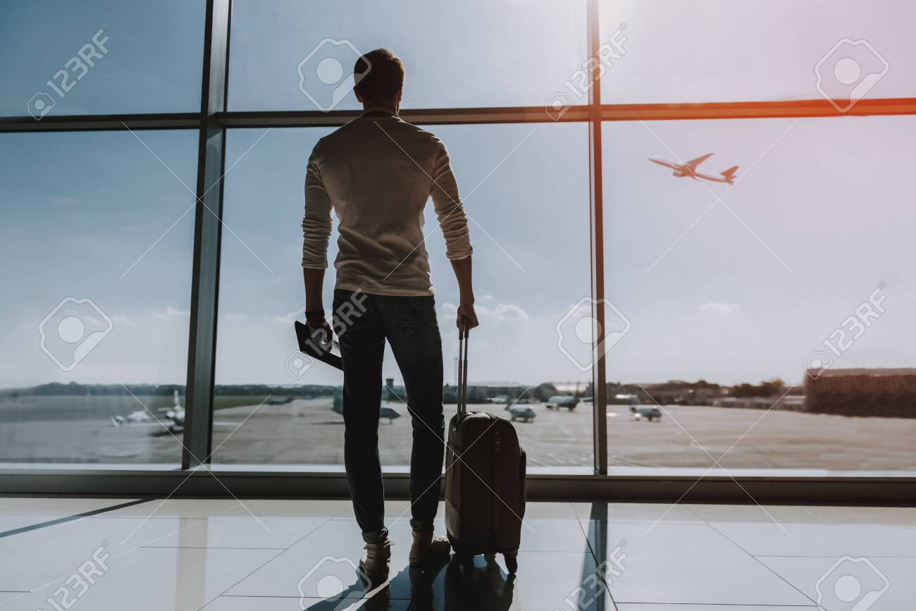 Guy is standing near big window at airport. He is looking outside and observing transport. Copy space in right side - 127177101