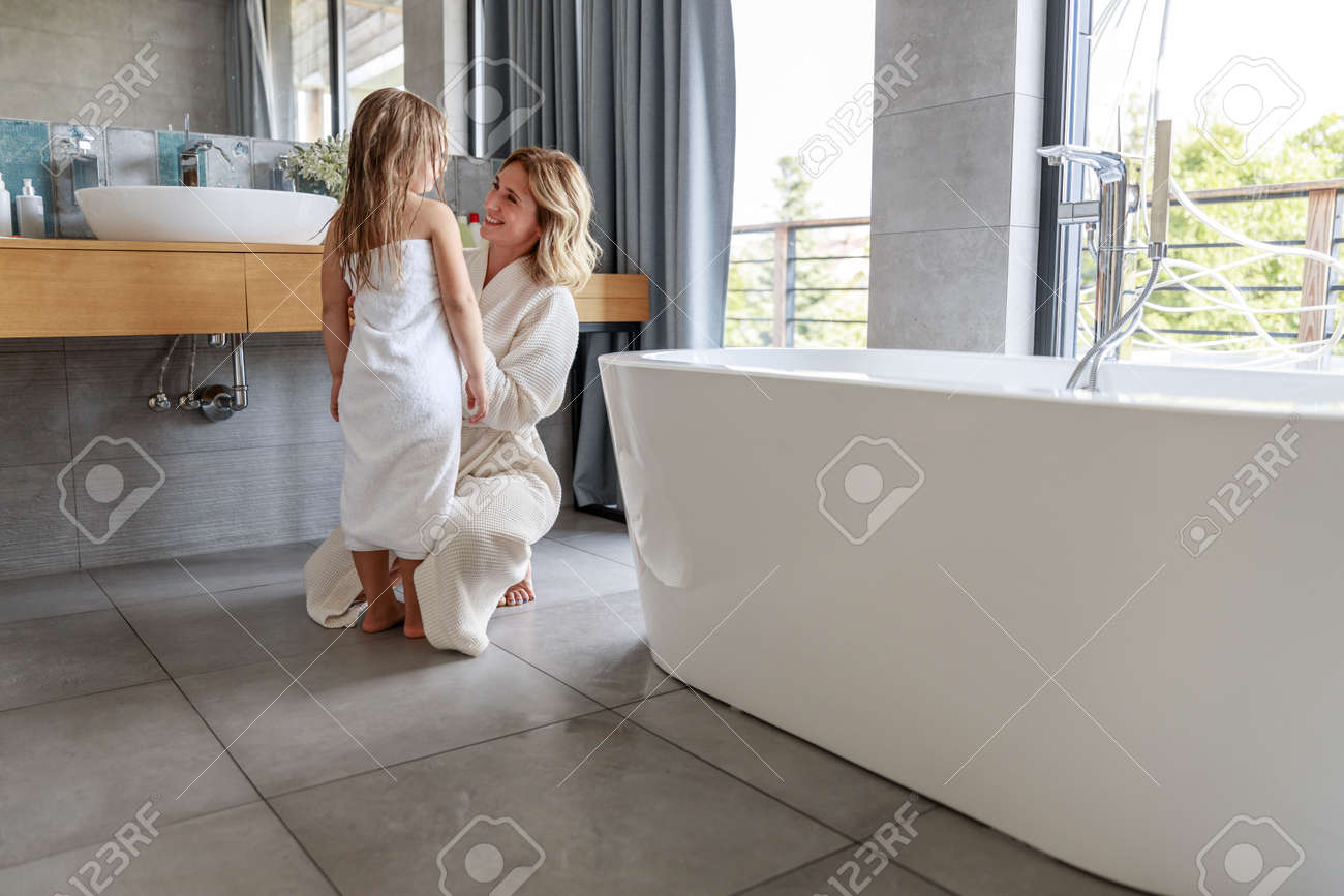 Mother in bathrobe in bathroom at home - 129549935