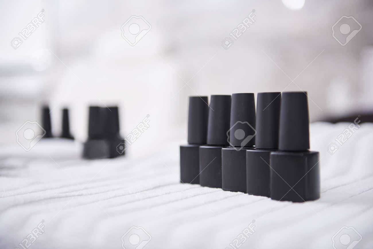 Black bottles of nail varnish on white soft towel - 130478226