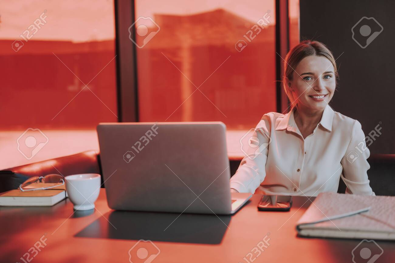 Joyful young woman working on laptop in office - 137250043