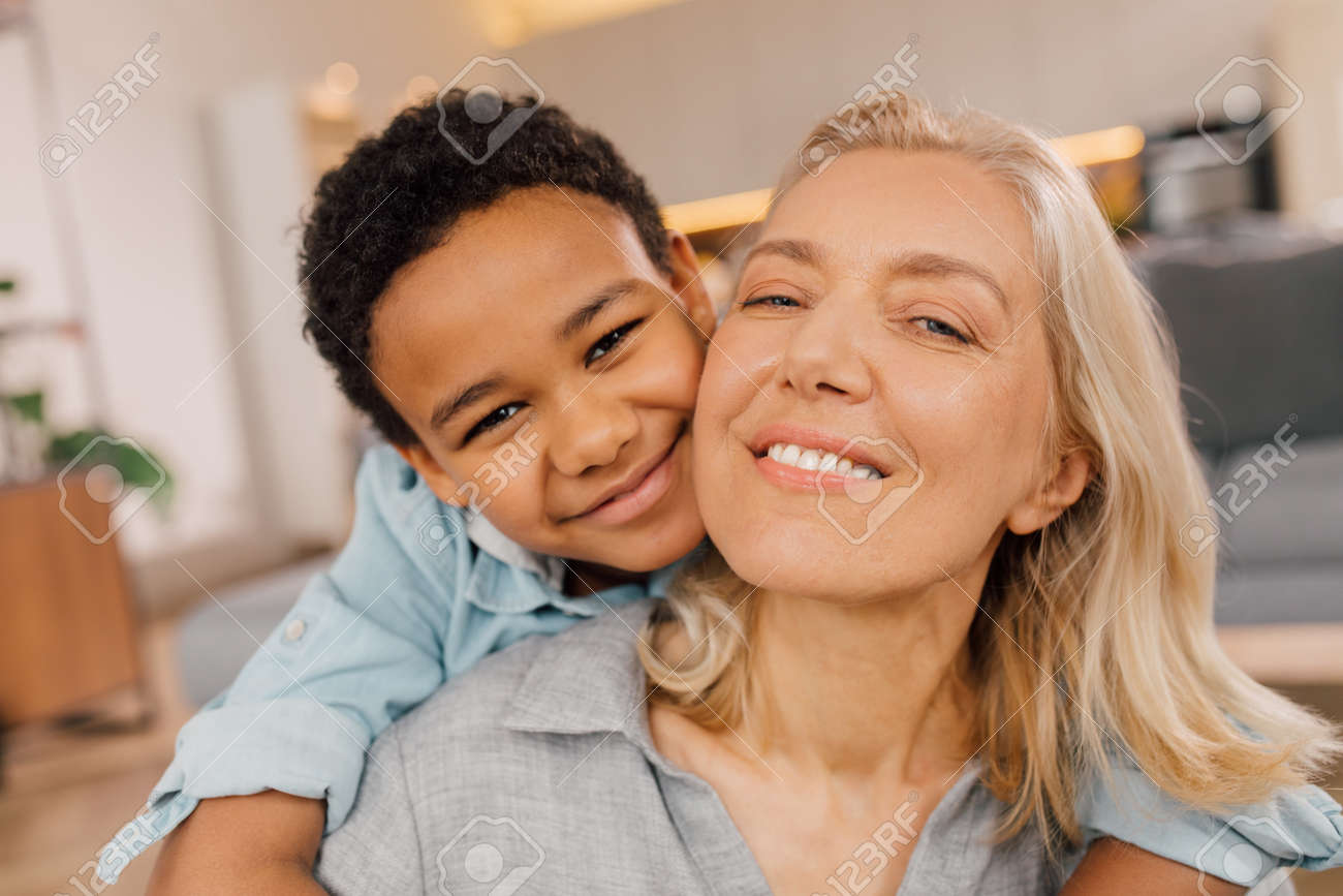 Mother looking at the camera while her multiracial son embracing her - 167697264