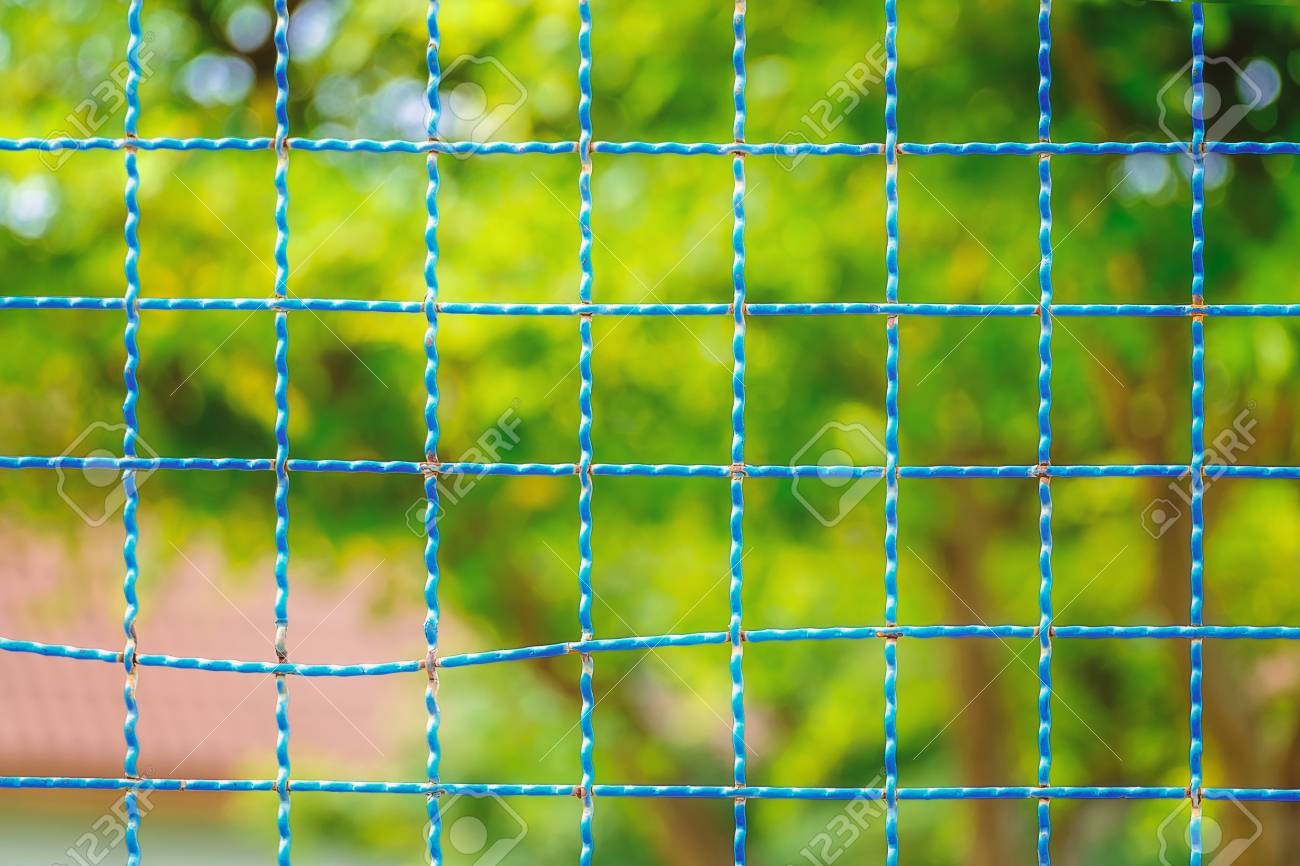 Steel wire mesh fence with green natural blur background