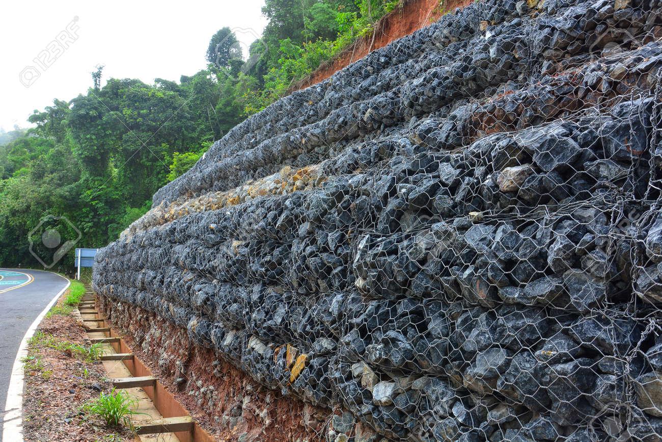 foto de archivo muro de gaviones de piedras en la malla de acero que se utiliza como una valla en una pendiente para el de tierra de - Muro De Gaviones