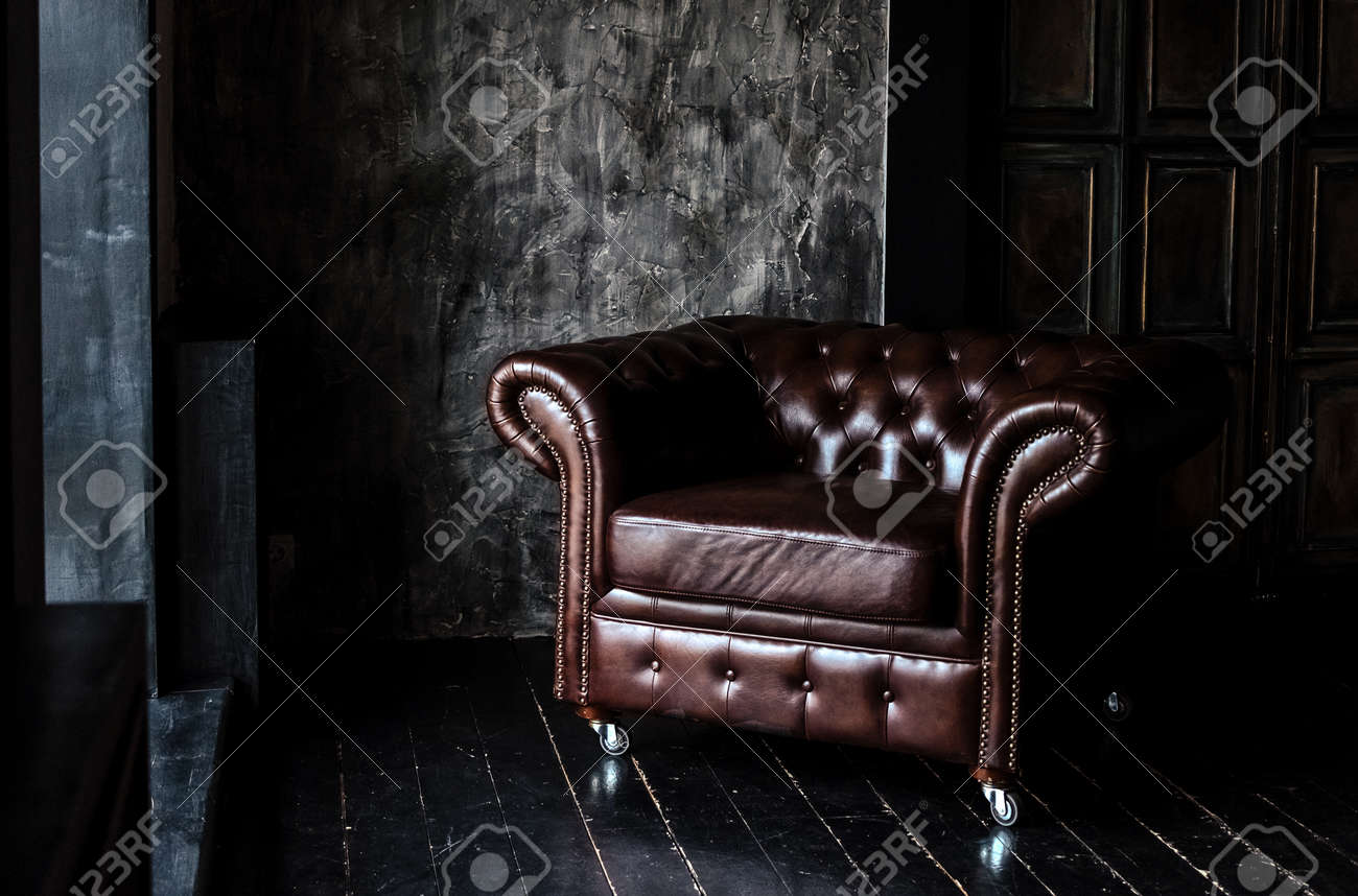 Sofa Of Brown Leather Standing In Center On Concrete Floor Against