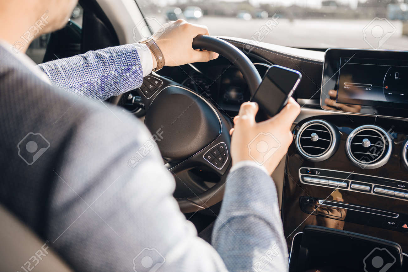 Young businessman looking at mobile phone while driving a car. - 129386240