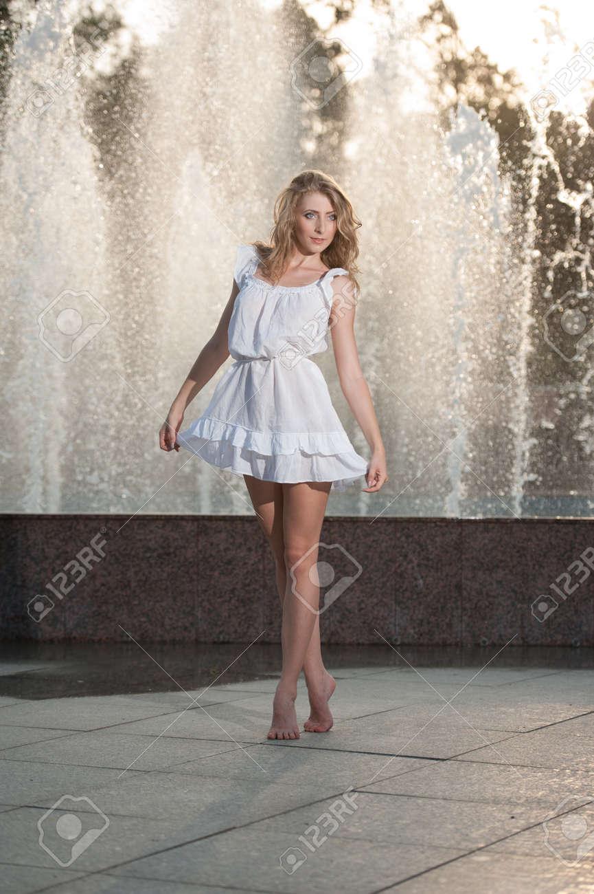 reputable site 87c4d 70b36 Attraente ragazza in abito corto bianco seduto di fronte a una fontana in  estate più calda giornata Ragazza con il vestito da ballo parzialmente ...