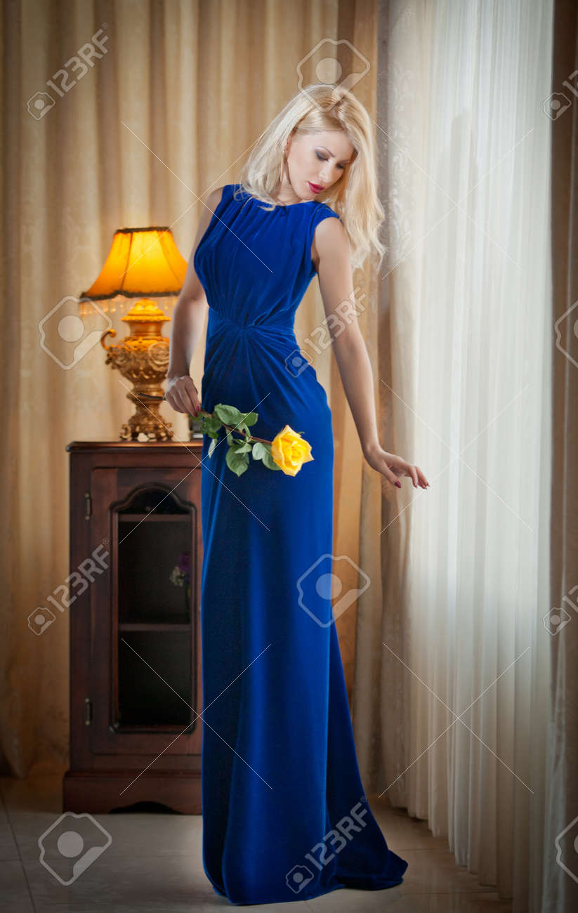 Stock Photo - Young beautiful luxurious woman in long elegant blue dress  holding an yellow flower Beautiful young blonde woman with curtains in  background ... 0e10001aa