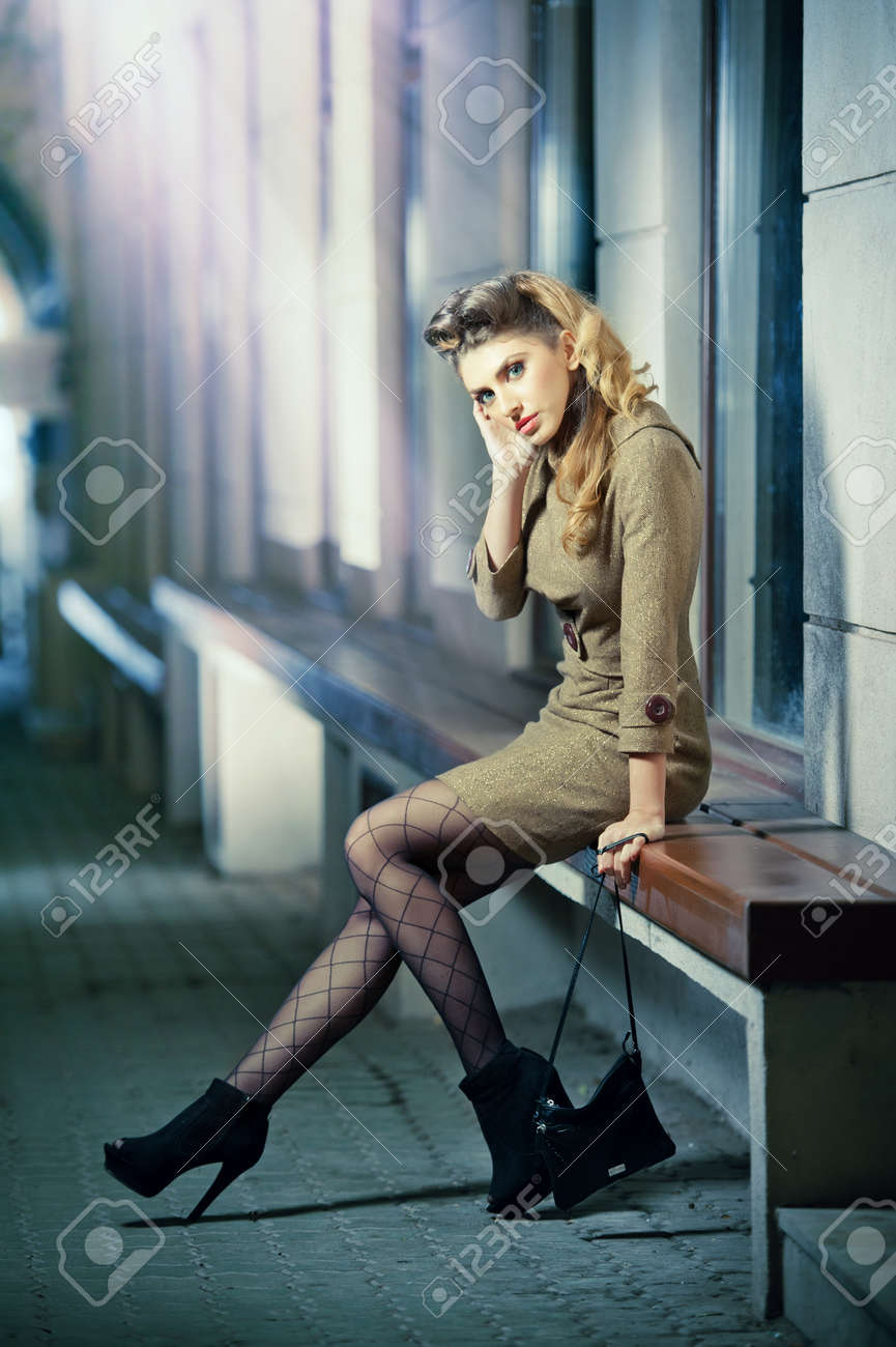 Attractive blonde girl wearing short dress and high heels - urban scene  Fashion model with long