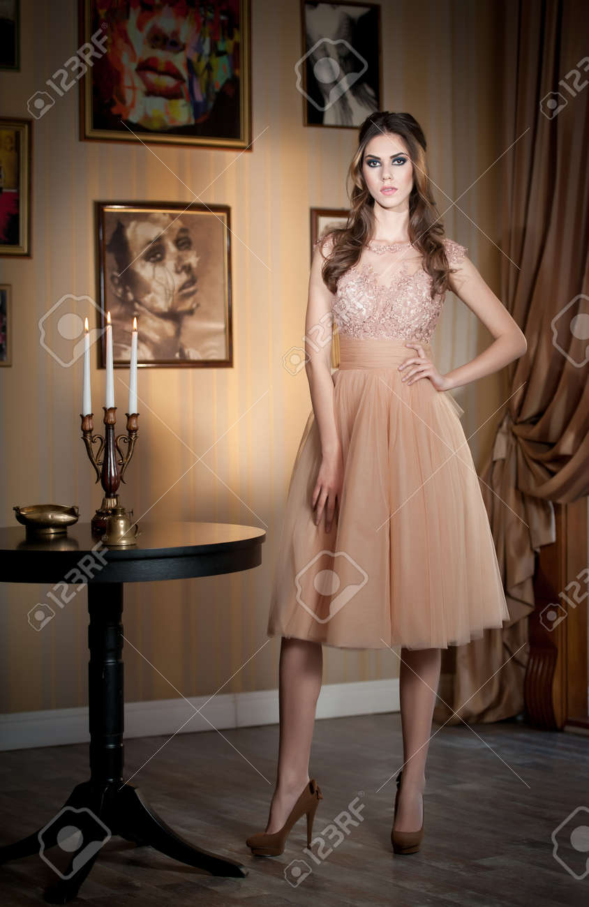 Beautiful brunette lady in elegant nude colored dress posing in a vintage  scene Young sensual fashionable