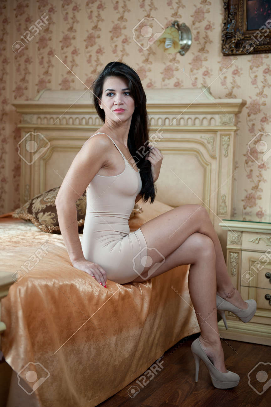 junge schöne reizvolle frau im weißen kurzen engen kleid posiert  anspruchsvolle innen im vintage-hotelzimmer. sinnliche brünette auf high  heels im