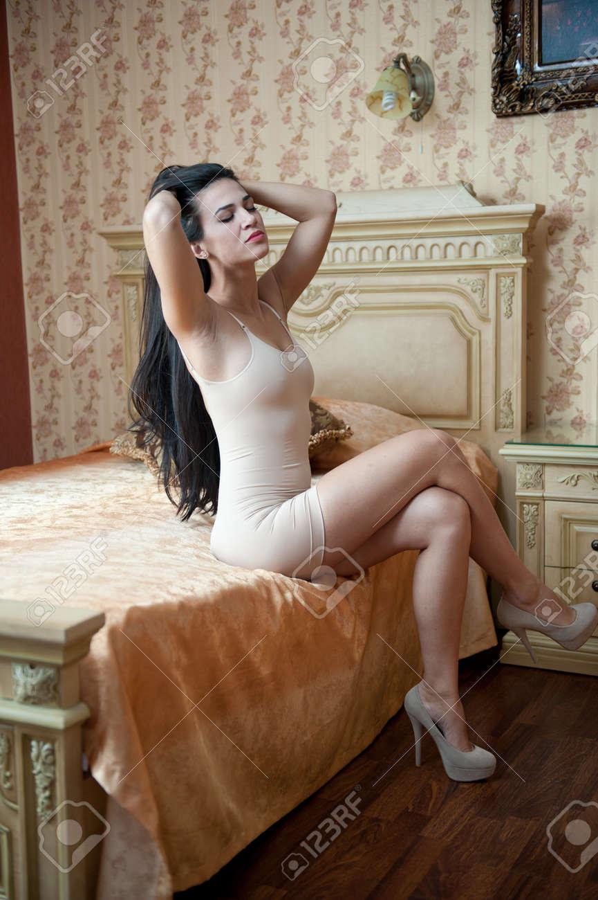 junge schöne reizvolle frau im weißen kurzen, engen kleid posiert  anspruchsvolle innen im vintage-hotelzimmer. sinnliche brünette auf high  heels im